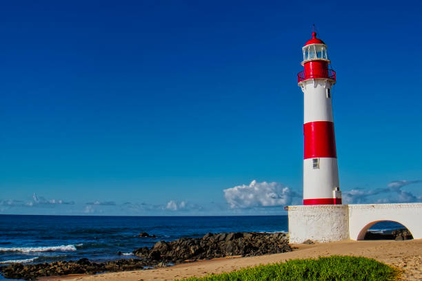 Lighthouse Itapua beach with blue sky, Salvador, Bahia, Brazil Lighthouse Itapua beach with blue sky, Salvador, Bahia, Brazil beacon stock pictures, royalty-free photos & images
