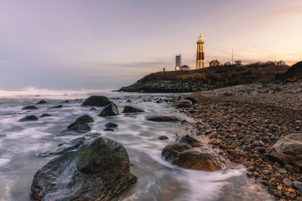 Lighthouse lit up with Christmas lights in a winter seascape along a rocky coast. Montauk State Park, New York.