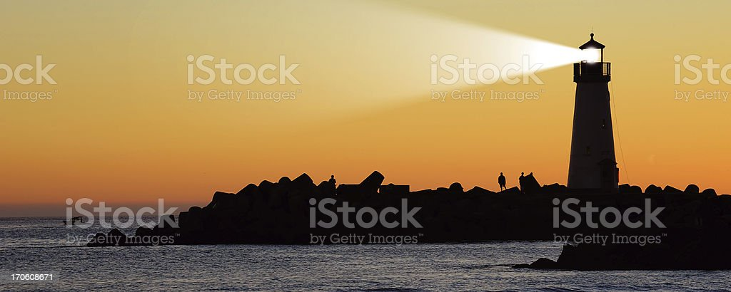 Lighthouse on a rocky shore silhouetted against the sunset stock photo