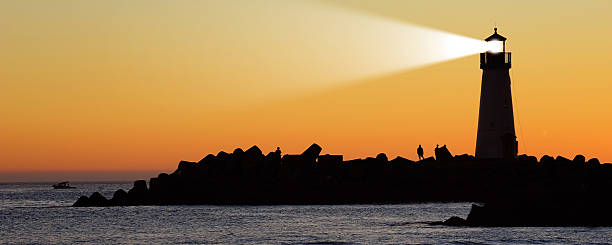 Lighthouse on a rocky shore silhouetted against the sunset Light house, Santa Cruz, California, USA beacon stock pictures, royalty-free photos & images