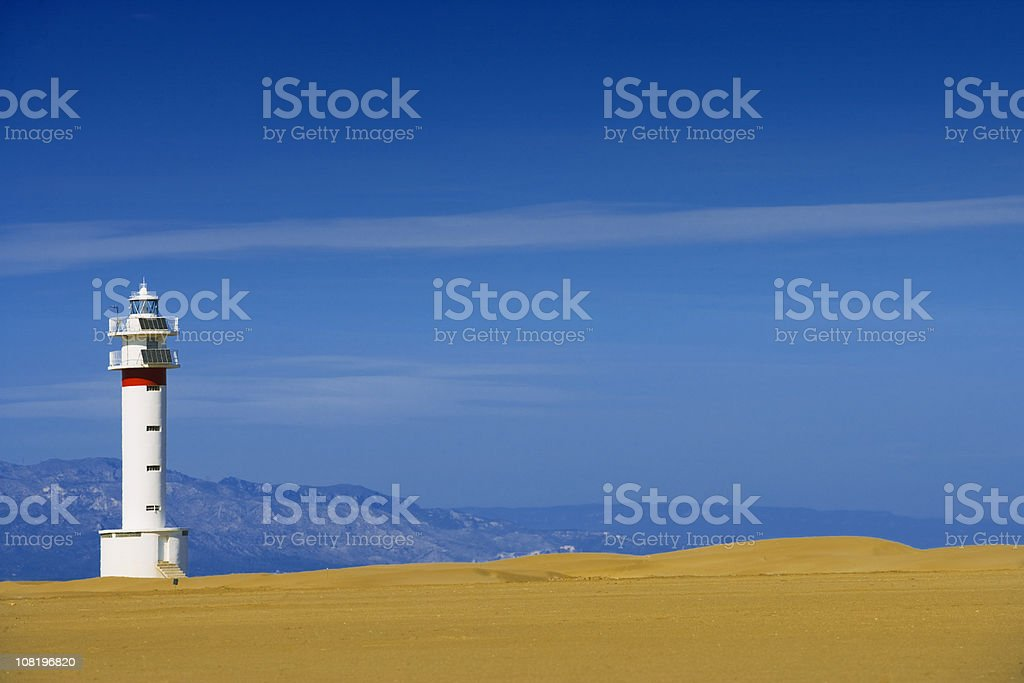 Lighthouse on Beach with Coastline in Background royalty-free stock photo