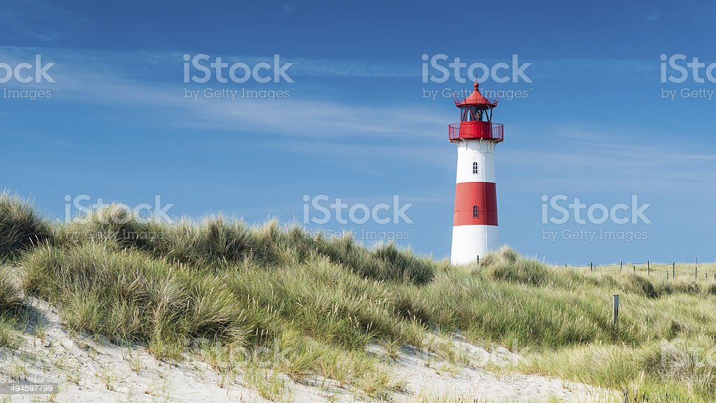 Lighthouse on dune horizontal stock photo