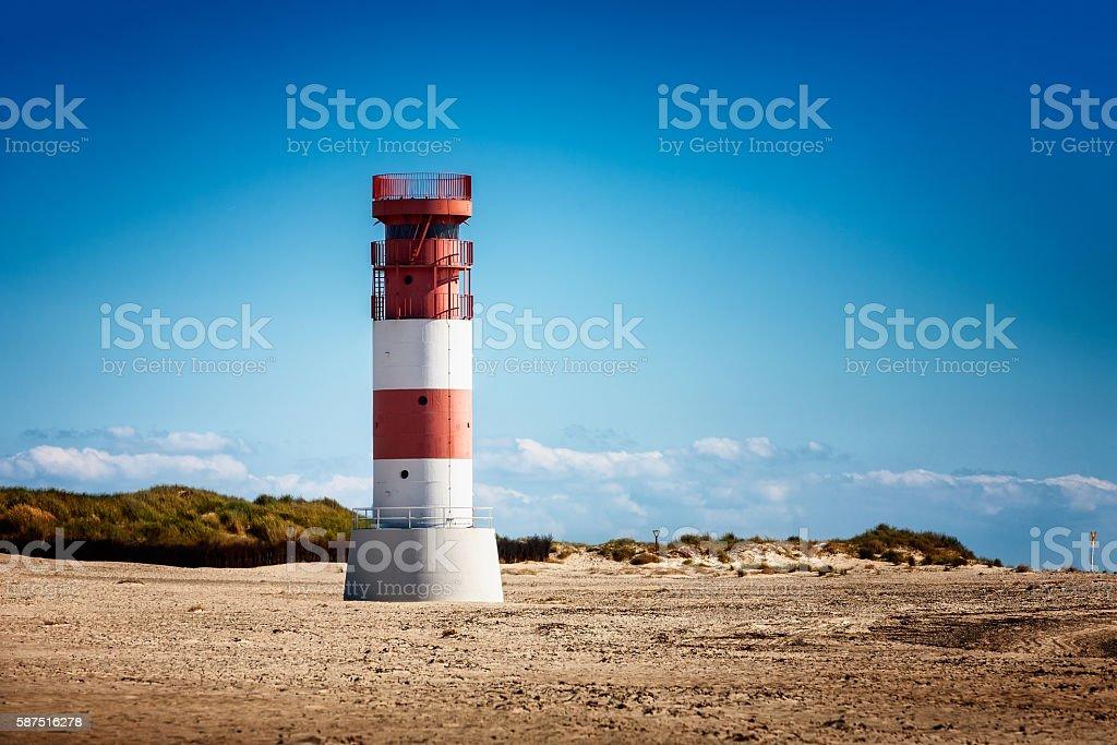 Lighthouse on dunes beach stock photo