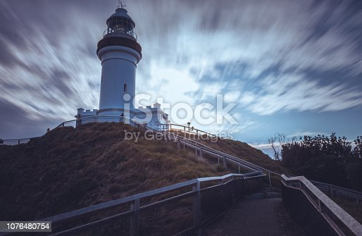 1030314738 istock photo Lighthouse on hill of shore under clouds 1076480754