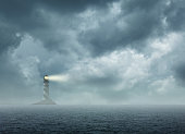 A lighthouse sits on a small rocky island on the horizon as it shines its light during inclement weather.