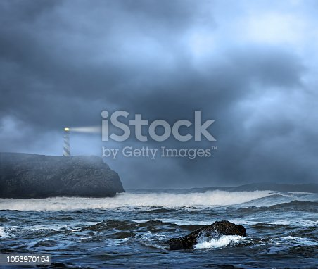 A lighthouse sits on top of  a rocky cliff that overlooks a rough ocean in foggy and inclement weather.  The cloudy and foggy sky provide ample room for copy and text.