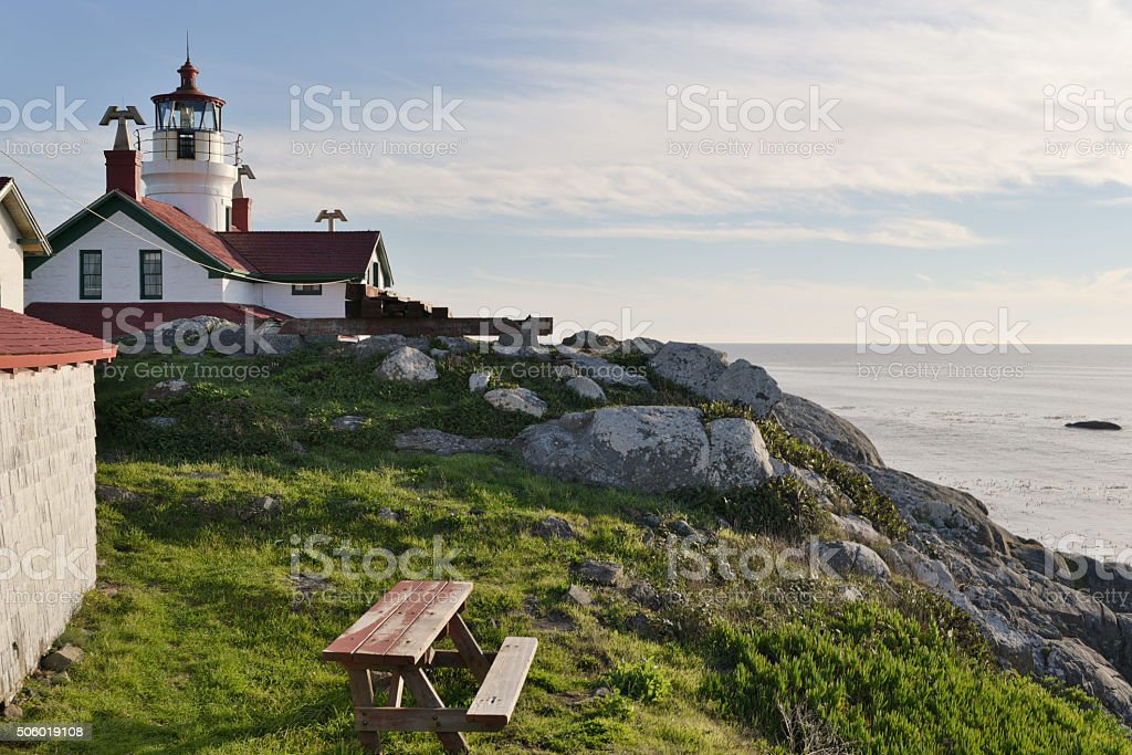 lighthouse on rocky island with picnic bench and ocean view stock photo