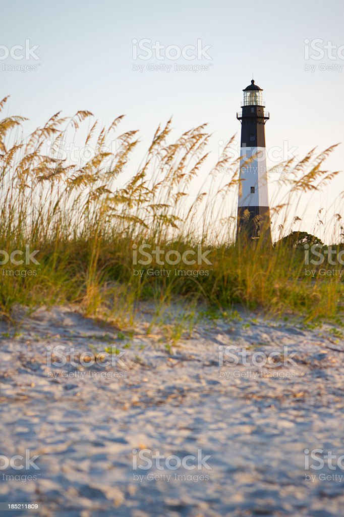 A lighthouse on the beach with sand and grass stock photo