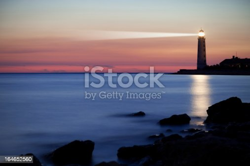 A seascape is pictured at the end of sunset.  There is a lighthouse casting light into the background and reflecting onto the waters in front of it.  In the foreground there are silhouetted rocks, in the middle ground there is soft blue-white water and in the background is the lighthouse and colorful sky filled with pink, orange and green.