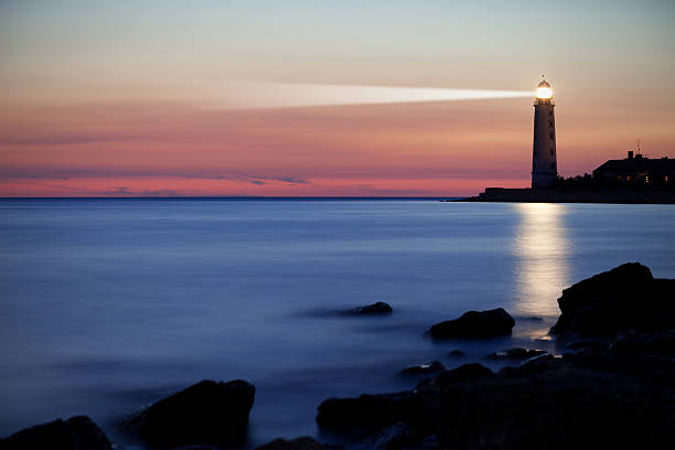 A lighthouse on the coast at sunset stock photo