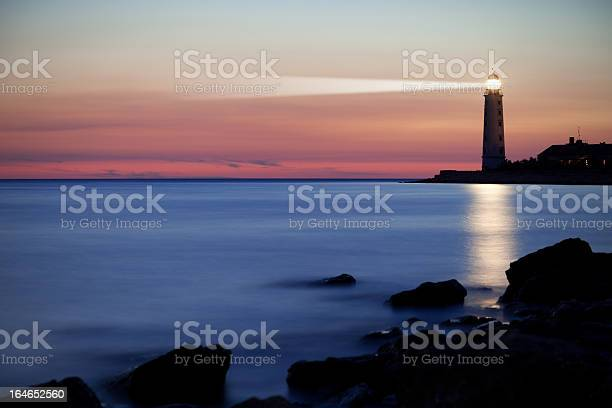 Photo of A lighthouse on the coast at sunset