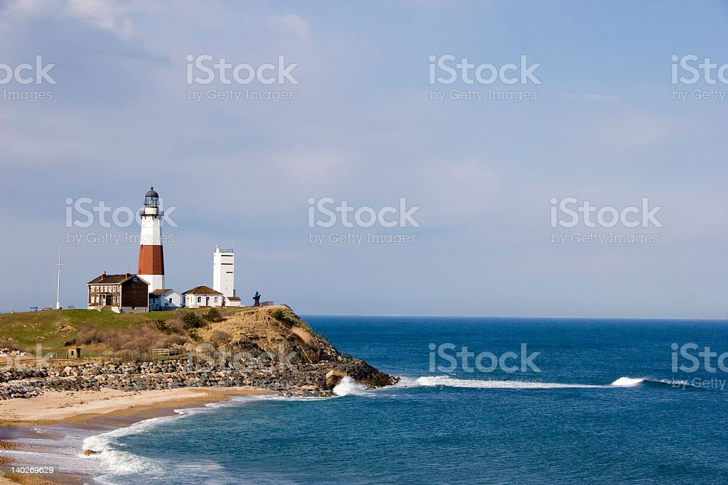 A lighthouse on the edge of a cliff with the view of sea stock photo
