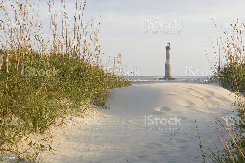 Lighthouse on the sandy beach surrounded by greenery growth stock photo
