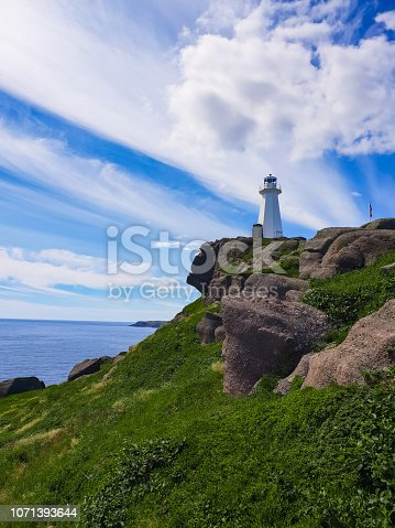Lighthouse in Newfoundland in Canada, overlooking the ocean on top of a hill on a beautiful sunny day!
