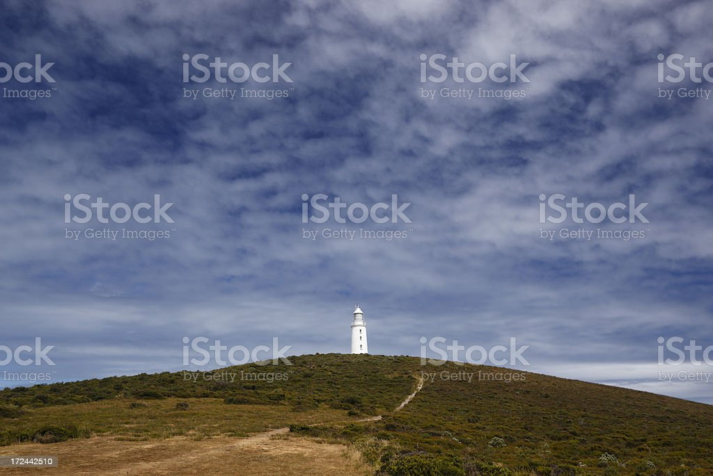 Lighthouse on windswept hilltop with unusual clouds stock photo