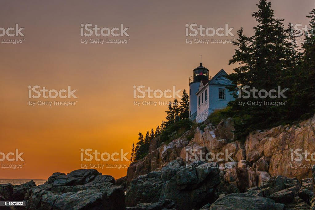 Lighthouse over cliff at Acadia National Park with sunset stock photo
