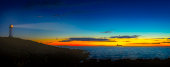 Panorama with dramatic light and sky with a beautiful old lighthouse in front, sunset, ship in background at the horizon