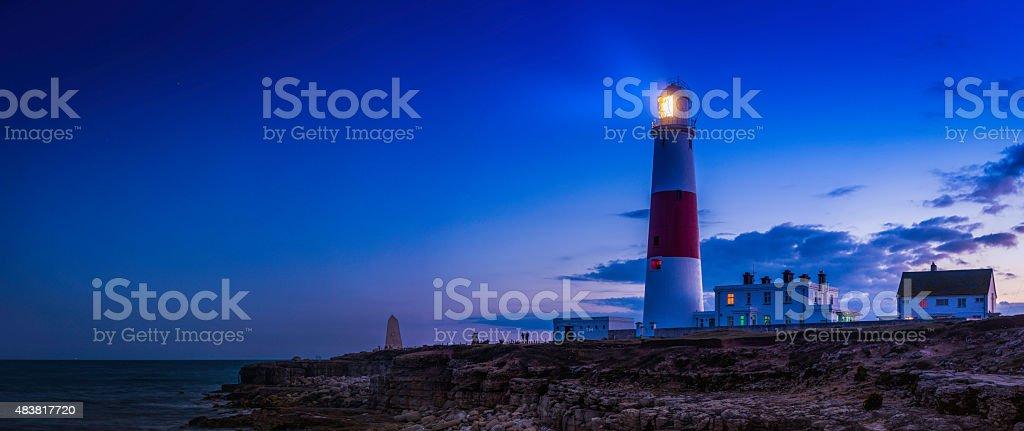Lighthouse shining over ocean shore sunset Portland Bill Dorset UK stock photo