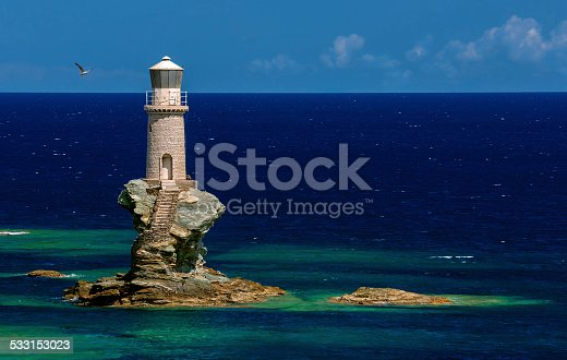 The beautiful Lighthouse Tourlitis of Chora in Andros island and a seagull, Cyclades, Greece