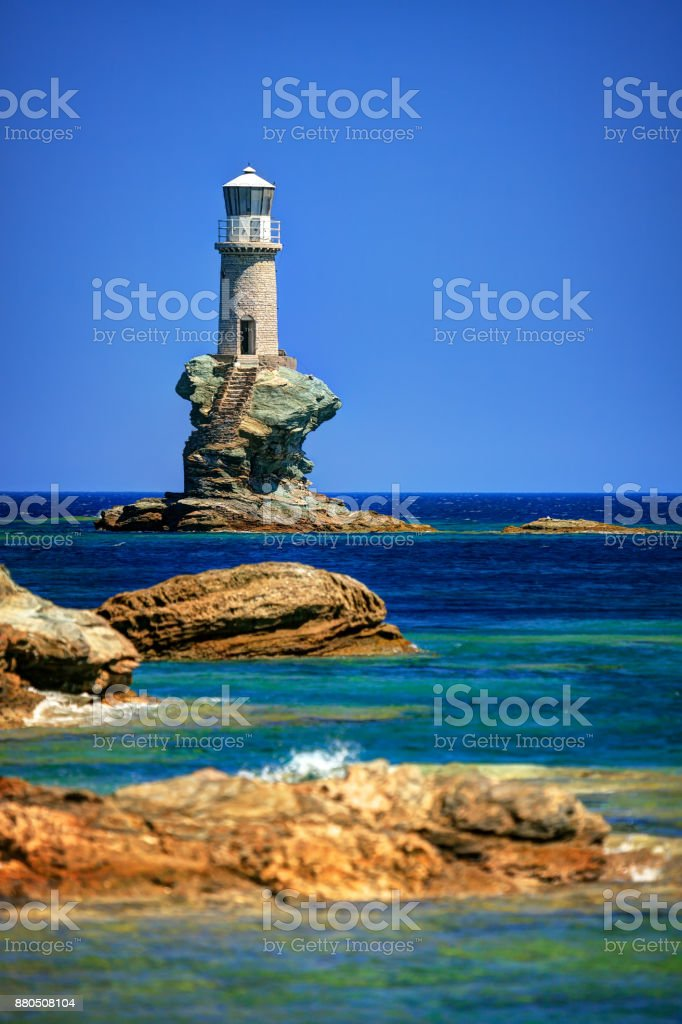 Lighthouse Tourlitis standing on a single rock, in Chora, Andros island, Cyclades, Greece stock photo