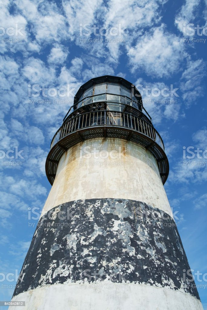 Lighthouse tower against blue cloudy sky stock photo