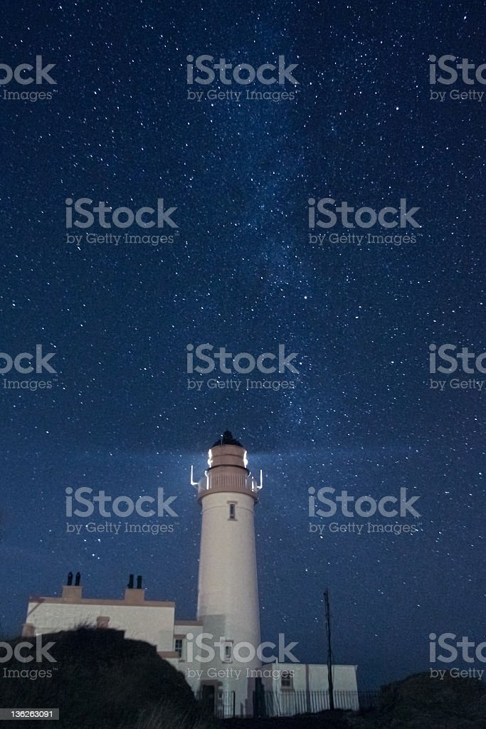 Lighthouse under the stars stock photo