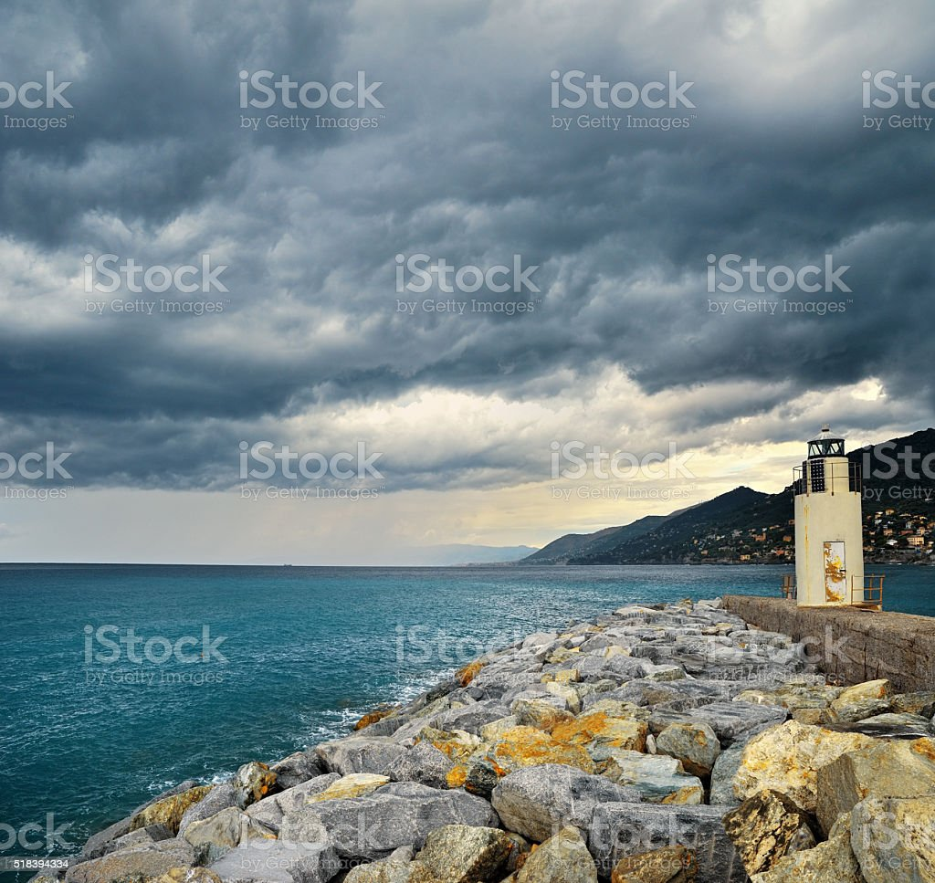 Lighthouse with storm dark clouds stock photo