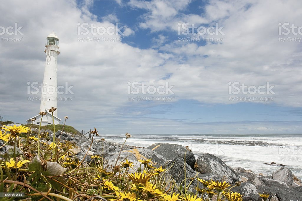 Lighthouse with yellow flowers and ocean stock photo