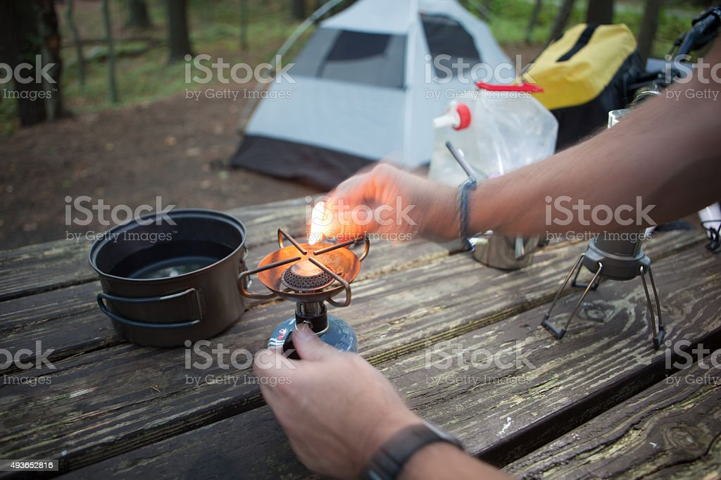 Lighting a butane stove while camping. stock photo