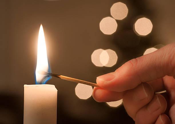 lighting a candle - hand tänder ett ljus bildbanksfoton och bilder