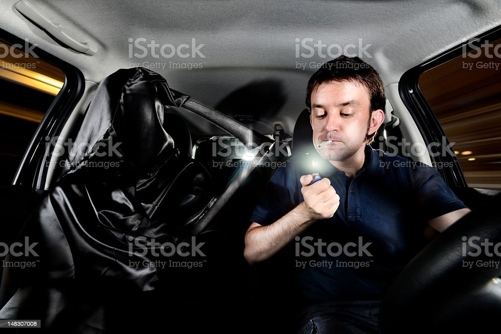 Lighting a cigarette while driving royalty-free stock photo