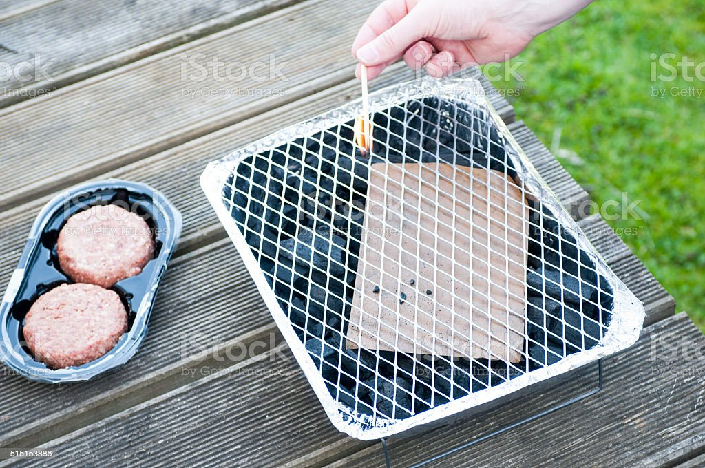 Lighting A Disposible Barbecue stock photo