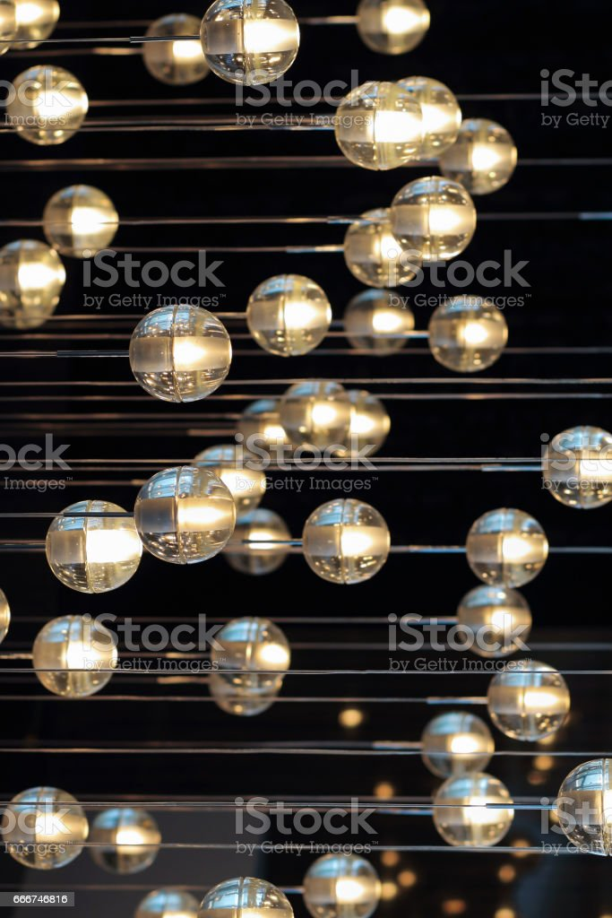 lighting balls on the chandelier in the lamplight,  light bulbs hanging from the ceiling, lamps on the dark background, selective focus, horizontal foto stock royalty-free