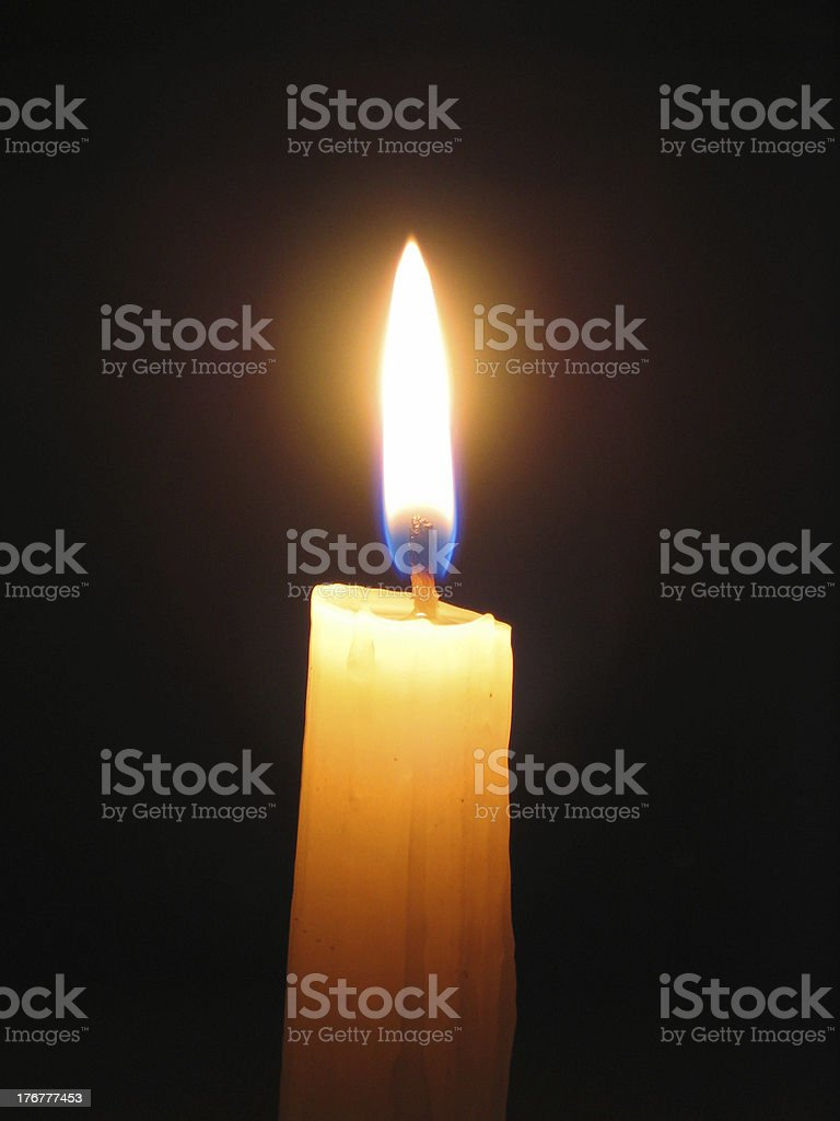 lighting candle against dark background stock photo
