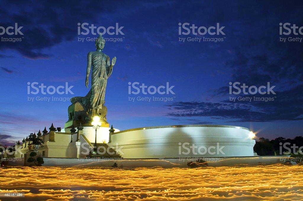 Lighting candle and Buddha statue stock photo