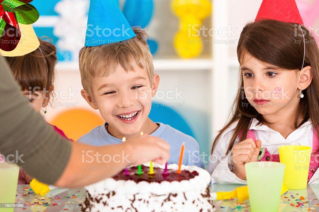 Lighting candles on birthday cake royalty-free stock photo