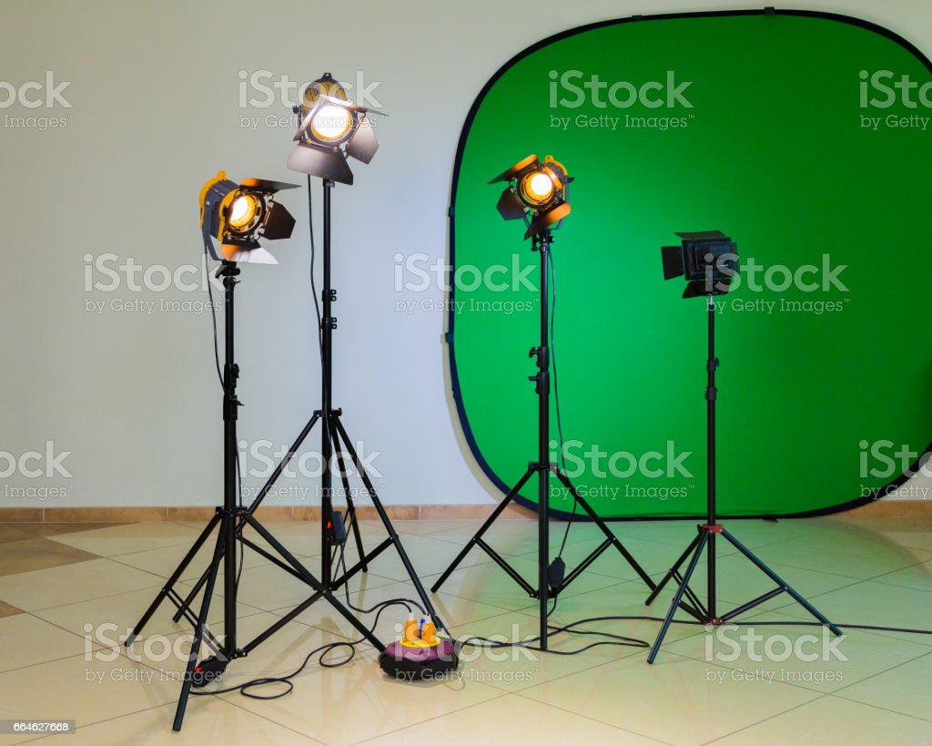 Lighting equipment for filming in the interior. Green background for chromakey. Halogen spotlights with Fresnel lenses. Electrical cables and extension cords stock photo