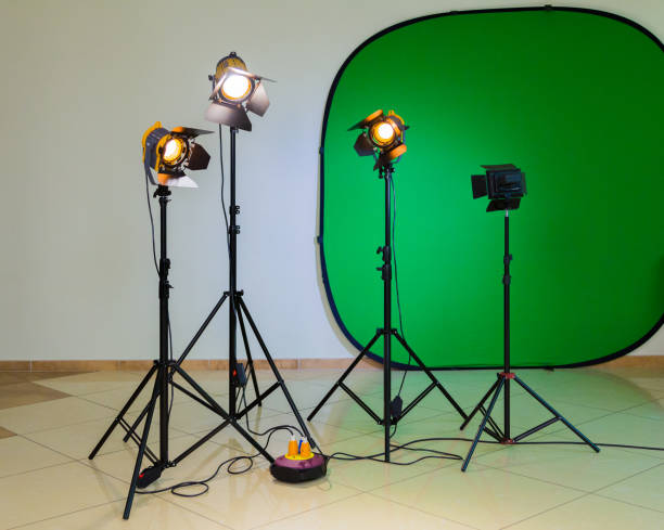Lighting equipment for filming in the interior. Green background for chromakey. Halogen spotlights with Fresnel lenses. Electrical cables and extension cords