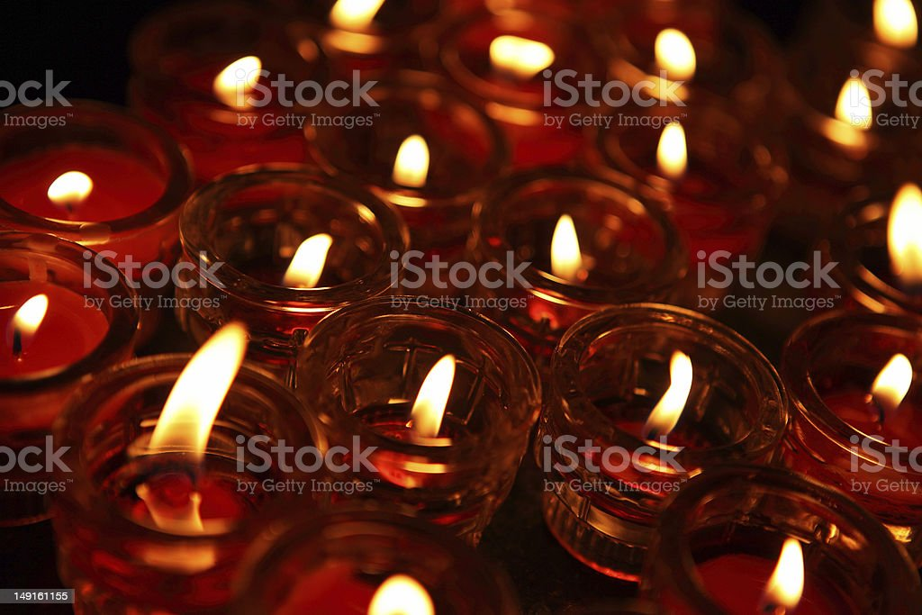 Lighting of Praying candles in a temple. stock photo