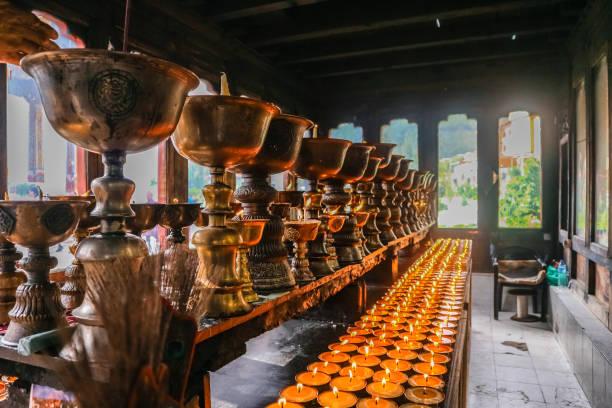Lighting of praying candles in Zangdhopelri Monastery in Thimphu, Bhutan stock photo