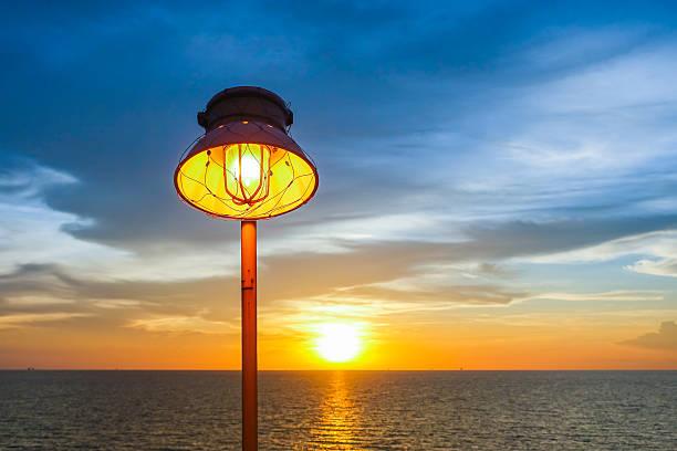 lighting of warm lamp and lighting of sunset at sea. - disaster design stock-fotos und bilder