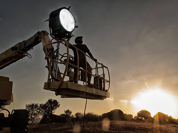 Lighting technician working on a shoot stock photo