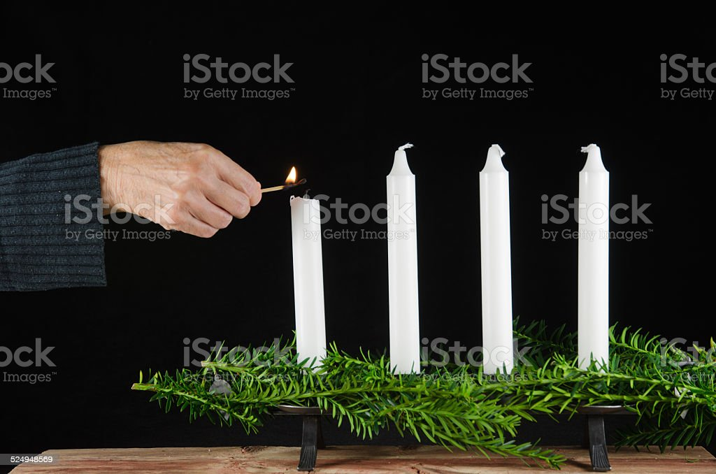 Lighting the first advent candle stock photo