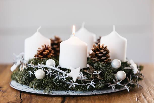 belysning första ljuset på advent kransen på den första söndagen i december för att fira beginiing av julhelgen i schweiz - advent bildbanksfoton och bilder