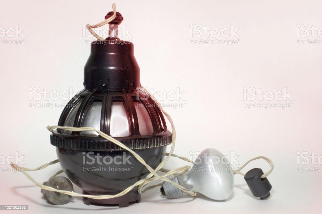 unidade de iluminação anteriormente utilizada em laboratórios de fotografia para impressão de fotos. Equipado com suporte de energia cabo e lâmpada, que se esconde dentro. lâmpada com o refletor entre os fios. Vermelho, iluminação, distintivo para  - foto de acervo