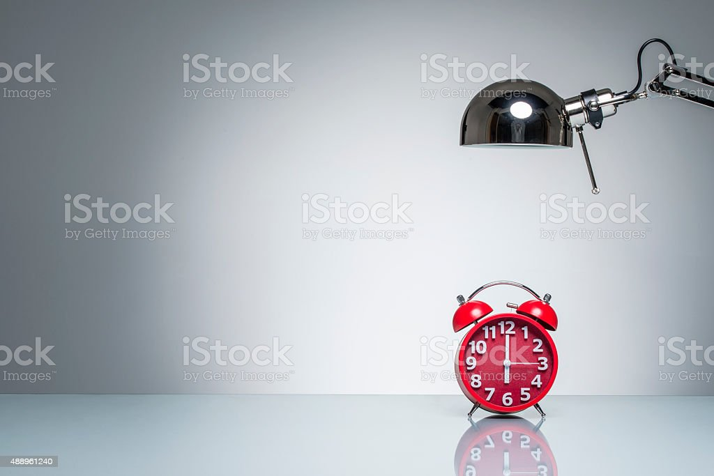 lighting up red alarm clock with desk lamp stock photo