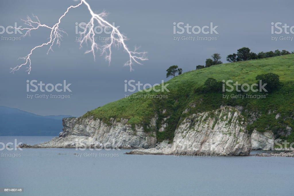 Lightning above green foreland. Seascape. stock photo