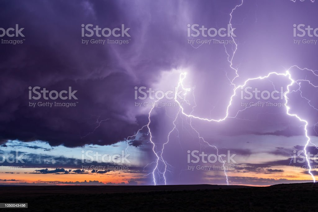 Lightning and thunderstorm with rain and colorful sky at sunset.