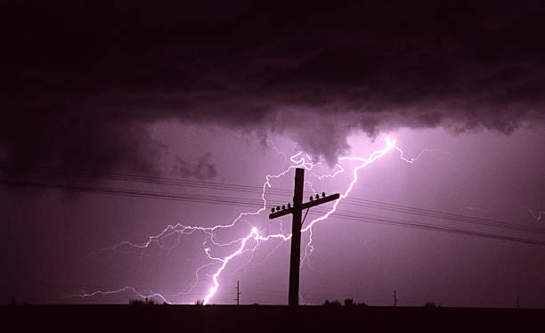 Lightning behind cross-shaped electric pole stock photo