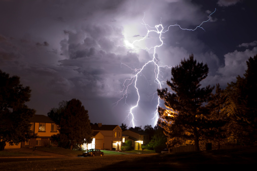 A massive thunderhead pours rain and lightning over suburban Denver homes, Colorado. Trees are silhouetted and homes are lit by incandescent light. The thunderhead is lit by huge lightning bolts reaching from the top of the clouds to the ground.